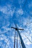Segeljachtmast gegen blauen Himmel und Wolken Stockfotos