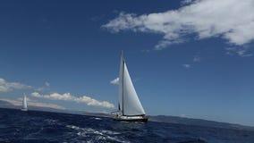 Segeln in den Wind durch die Wellen in dem Ägäischen Meer in Griechenland Reihen von Luxusyachten am Jachthafendock stock footage