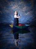Segeln des kleinen Mädchens unter Verwendung des Regenschirmes Lizenzfreie Stockfotografie