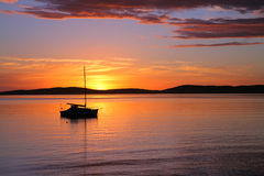 Segelnboot verankert am Sonnenaufgang Lizenzfreies Stockbild