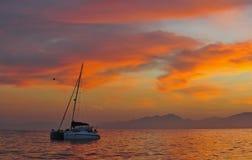 Segelnkatamaran in dem Ozean an der Küste von Südafrika bei Sonnenaufgang lizenzfreies stockfoto