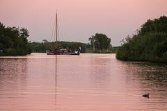 Segelschiff an der Glättung des Sonnenuntergangs auf Wasser von Eernewoude in Friesland lizenzfreie stockbilder