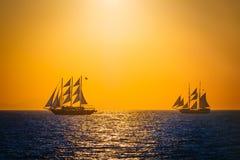 Segelschiffe auf dem Meer im Sonnenuntergang Stockfotos