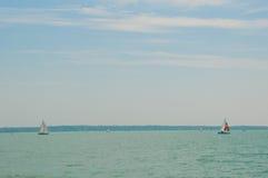 Segelsportwettbewerb auf Plattensee, Ungarn Zwei Segelboote auf Vordergrund unter schönem blauem Himmel mit Wolken Stockfoto