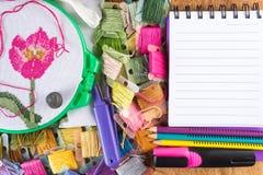 Segeltuch mit gestickter roter Blume, Bändern, Threads, Bleistiften, Markierung und Notizblock auf Holztisch Stockbilder