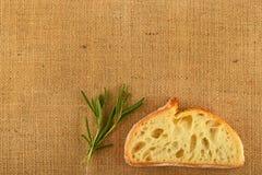 Segeltuch mit Rosmarinblättern und Scheibe des Weizenbrotes Stockfotografie