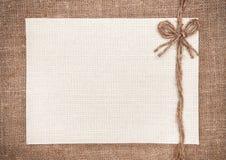 Segeltuchkarte auf Hintergrund des groben Sackzeugs Stockfoto