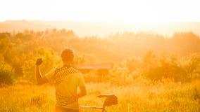 Seger över dig En cyklist håller ögonen på en underbar landsca royaltyfria foton