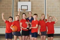 Segerrika skolasportar Team With Trophy In Gym Arkivbilder