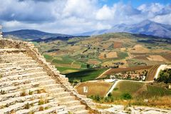 Segesta Ruins on Hill Overlooking City. View of part of the amphitheater ruins on top of a hill overlooking the beautiful city of Segesta in Sicily, Italy Stock Photos