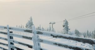 Seggiovia dello sci con gli sciatori in montagne innevate stock footage
