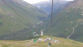 Seggiovia in una stazione sciistica vuota di estate Turisti che visitano la valle ed i ghiacciai stock footage