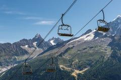 Seggiovia vuota in alpi francesi di estate Fondo delle montagne Fotografia Stock