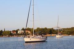 Segla ankras yachter i en pittoresk kanal av kusten av en liten by nära Sukosan DalmatianRiviera Kroatien arkivfoto