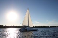 segla fartygöverskriften in på solnedgången arkivbild