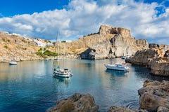 Segla fartyg i fjärden för St PaulÂs, molnig blå himmel, den Lindos akropolen Royaltyfria Bilder
