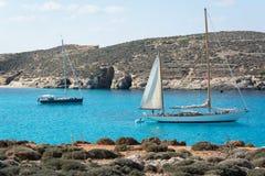 Segla fartyg som anslutas i en härlig kustlinje royaltyfri bild