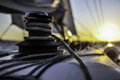 Segla fartyget med aktivering seglar glidning i det öppna havet på solnedgången royaltyfri fotografi