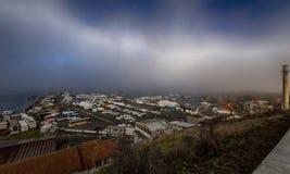 Segla hamnen på havskusten på en bakgrund av dramatisk dimma och blå himmel med vita moln Arkivfoto