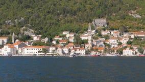 Segla i den Boka Kotor fjärden nära gammal stad med stenhus och tak av röda tegelplattor Arkivfoton