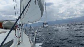 Segla i vinden till och med vågorna på det Aegean havet i Grekland seglar den mörka losed regattaseglingen för blå färg skysportv stock video