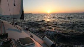 Segla i vinden till och med vågorna under solnedgång lager videofilmer