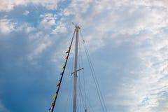 Segla master med festliga flaggor mot blå himmel med moln arkivfoton