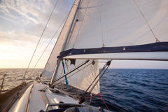 Segla på yachten på solnedgången fotografering för bildbyråer