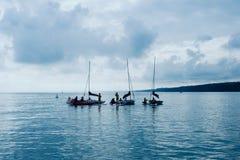 segla skola för ungar som öva på fjärden med lugna plant vatten och liten vind arkivfoton