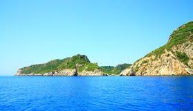 Segla utmed kusten med en bergskedja och en hemlig fjärd på den Korfu ön Fotografering för Bildbyråer