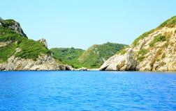 Segla utmed kusten med en bergskedja och en hemlig fjärd på den Korfu ön Arkivfoton