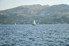 Segla yachten i havet mot bakgrunden av ett härligt knöllandskap arkivbilder