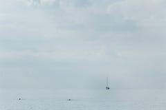 Segla yachten på horisonten Arkivbild
