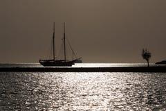 Segla yachten på solnedgången Arkivfoto
