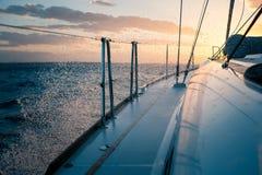 Segla yachten på solnedgången, vågorna och färgstänk arkivfoto