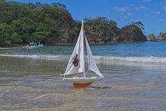 Seglar det orange skeppet f?r leksaken f?r att m?ta aff?rsf?retag p? en h?rlig strand royaltyfri fotografi