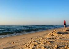 Seglar utmed kusten väntar ensamma ställningar på för en flicka på Blacket Sea och hennes vän Royaltyfria Foton