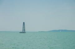 Segling lyx, segling, kryssningbegrepp En segelbåt väntar i daglugn under härlig blå himmel med moln på sjöBal Royaltyfri Fotografi