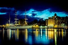 Seglingskepp i hamnen och en castele på natten Arkivbilder