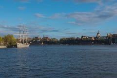 Seglingskeppet är i förgrund av Skeppsholmen öar på aftonen Royaltyfria Foton