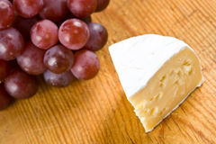 Segment of brie with grapes. On a wooden board royalty free stock photography