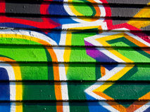 Segment of graffiti. Close up of graffiti painted onto the wooden slats on the side of a derelict building boarded up and disused Stock Photography