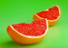 Segment of grapefruit. On green stock photos