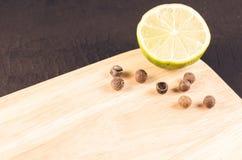 segment och kryddor på ett tomt limefruktsegment för bitande bräde och kryddor för limefrukt på en tom skärbräda på en mörk bakgr arkivbilder