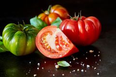 Segment of a sliced juicy ripe red tomato. With scattered seasoning and spice on a black surface with three fresh whole tomatoes of assorted colors Royalty Free Stock Photography
