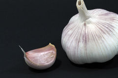 Segment and the whole garlic in a peel Royalty Free Stock Photography