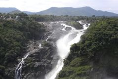 Segmented waterfalls with many channels of flowing water on mountains. With mountain range on background at Shivanasamudra Falls stock images