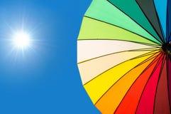 Segmentos coloridos del paraguas en el cielo azul Foto de archivo libre de regalías