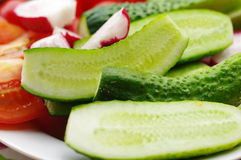 Segmentos de um pepino, de um tomate e de um rabanete frescos do jardim em uma placa Fotos de Stock Royalty Free