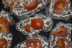 Segmentos del tomate puestos en el prendedero del pollo Fotos de archivo